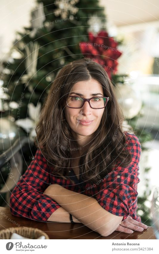 Pretty woman with glasses portrait with christmas tree in background woman portrait home 30s 40s attractive caucasian spanish one person one woman only people