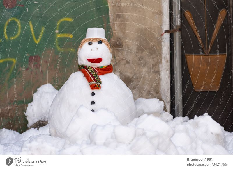 Snowman with scarf and hat stand alone at alley snowman face frozen ice winter leisure make snowman playful white wintertime cap cute home wall child season