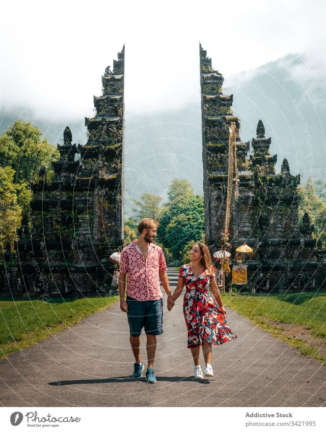Satisfied resting couple on walk among old exotic buildings travel tourism smile male female casual enjoy architecture construction nature temple religion