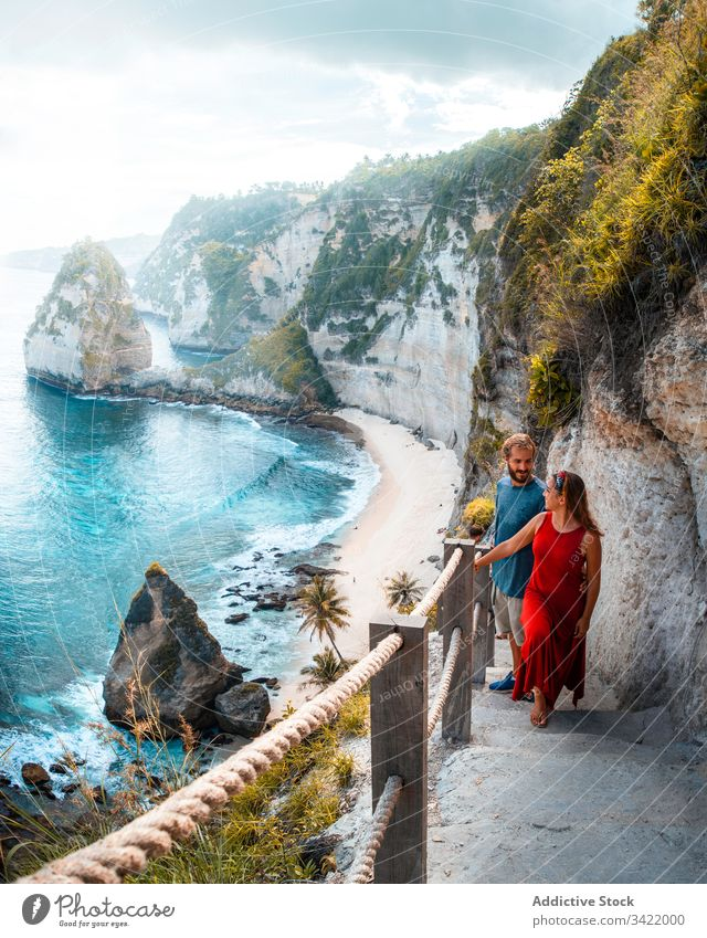 Happy resting couple walking on stairs among cliffs on seashore mountain lagoon male female tourism travel rock blue turquoise smile enjoy summer romantic love