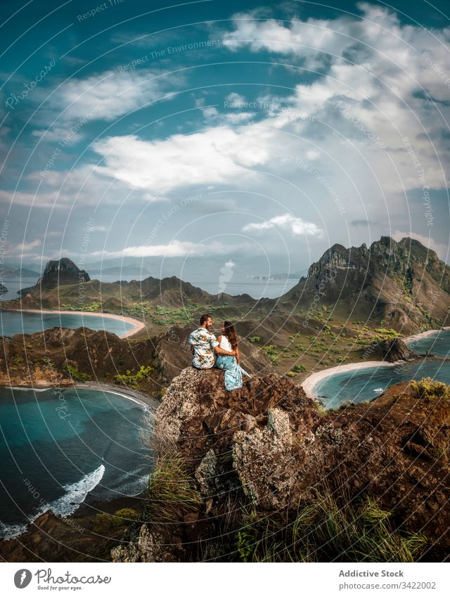 Peaceful couple on top of cliff among blue ocean and sky travel view mountain peak male female love relationship romantic enjoy island sea green nature