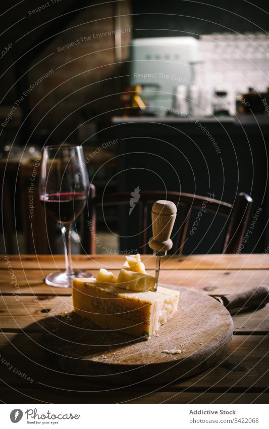 Cheese and glass of wine on table red wine cheese wooden rustic restaurant drink alcohol serve knife delicious tasty piece board service bar arrangement