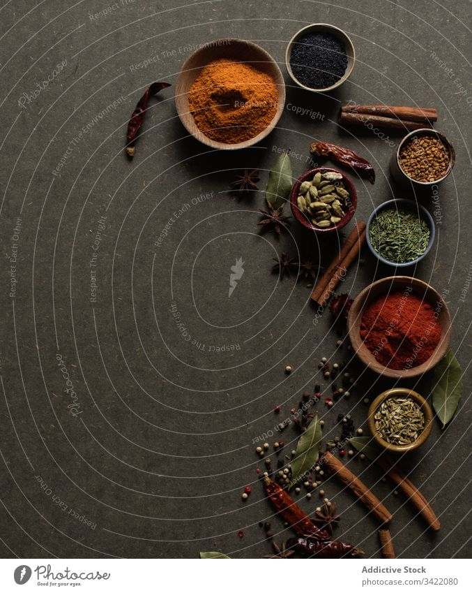 Various spices on gray background natural aromatic set assorted various powder seed dry food paprika pepper cinnamon peppercorn chili bay leaf stick bowl pot