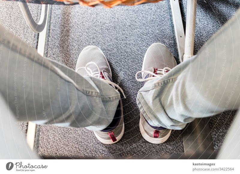 Male passenger with lack of leg space on long commercial airplane flight. Focus on casual sporty sneakers seat journey legs transport transportation travel