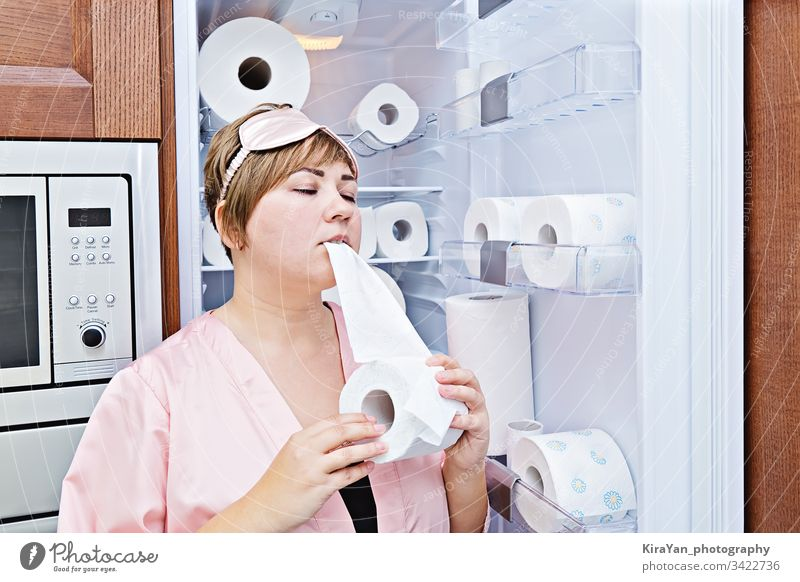 Woman in pajamas greedily eats toilet paper near the fridge filled with wc-paper night craving coronavirus woman covid-19 household hygienic tissue towel