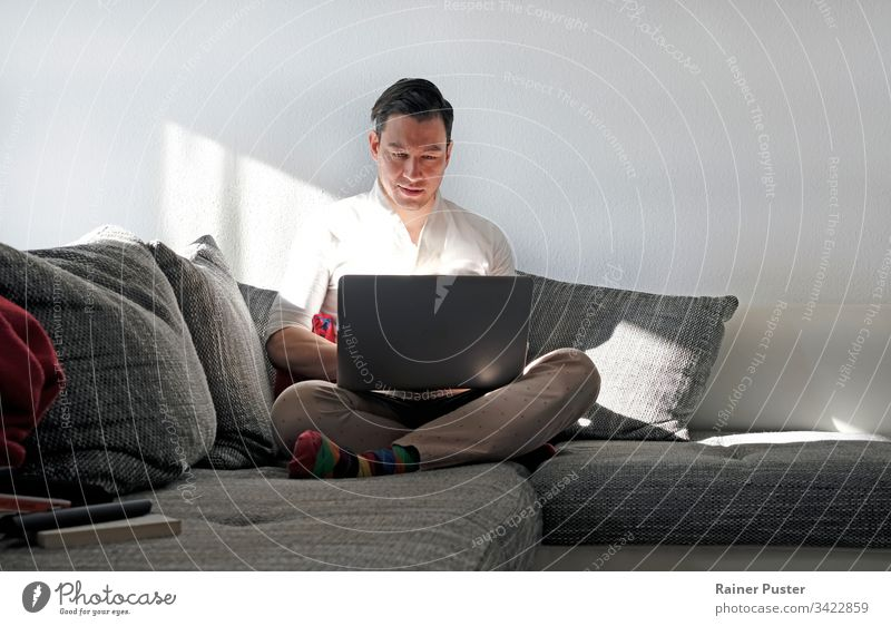 Man works from home with a laptop in the living room more adult Easygoing Computer Copy Space Entrepreneur freelancers Home Home office indoors Manly