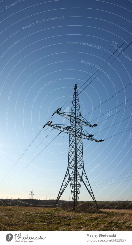 High voltage transmission tower on a field against the sun. industry sky power tower electricity pylon energy cable technology structure engineering wire