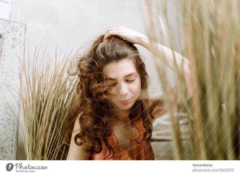 Young brunette woman shaking head and lipping her hair, selective focus curly casual grass light cheerful caucasian lifestyle adult girl portrait beauty dry