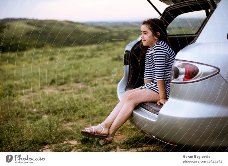 Little girl sitting in open trunk of car trip travel child happy journey tourist vacation happiness nature childcare enjoying daughter carefree break transport