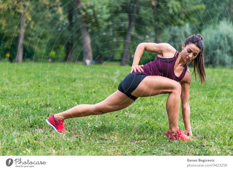 Young woman taking exercises in a park female summer outdoor training fitness grass forest green motion person exercising countryside attractive healthy