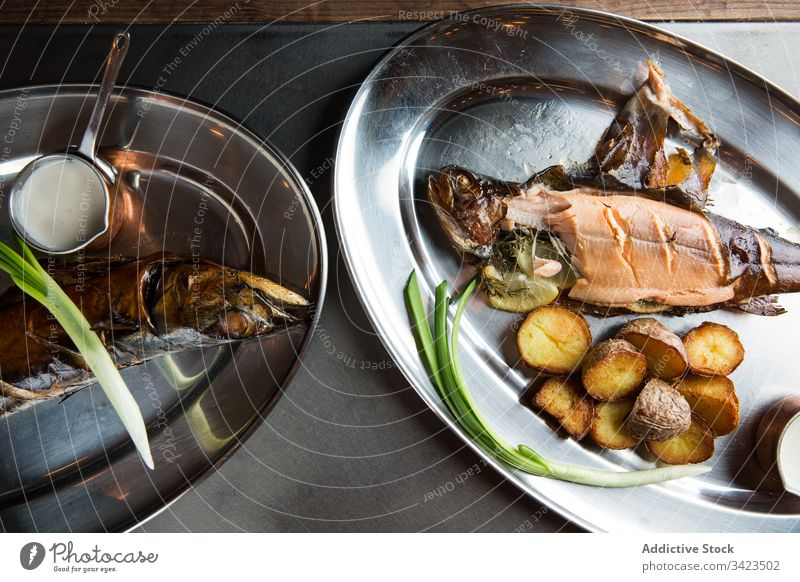 Roasted fish and potatoes with cream sauce and fresh scallion grill restaurant plate food meal delicious seafood gourmet tasty cafe cuisine nutrition dish