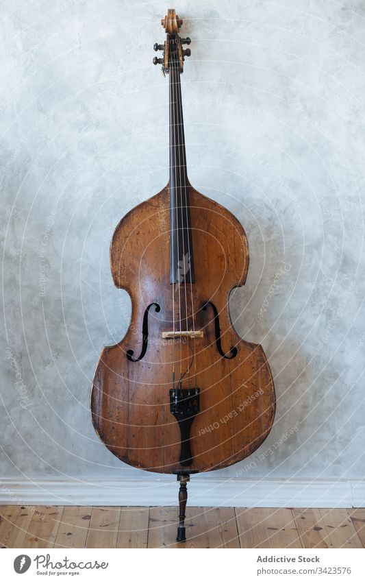 Brown wooden violin against wall music musician instrument grey classic string hobby equipment modern detail skill harmony tune culture entertain style home