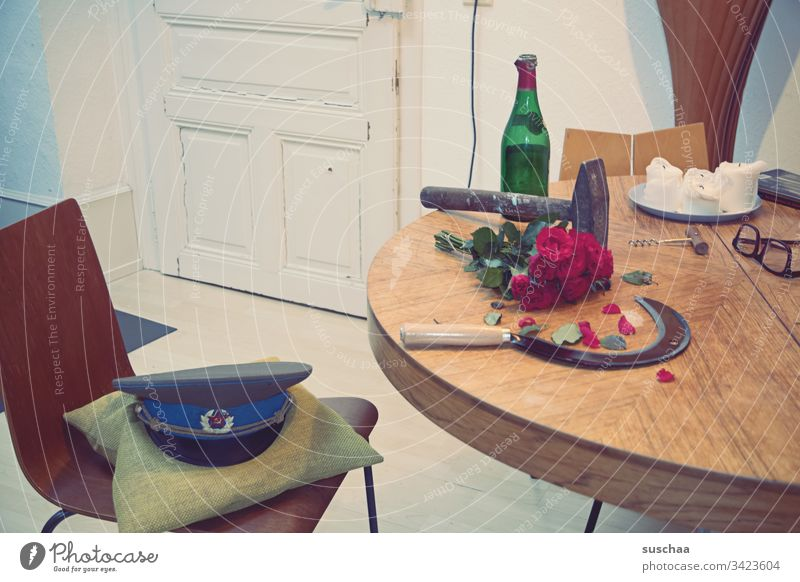hammer and sickle lying on a table, together with an empty wine bottle, a bouquet of red roses and a military cap Photochallenge Hammer Table Kitchen