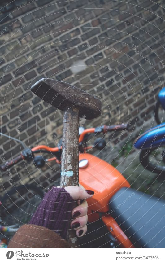 woman holding a hammer over an orange moped in front of a brick wall Woman feminine Hand Fingers Hammer Tool painted fingernails Motorcycle Handlebars Wheel