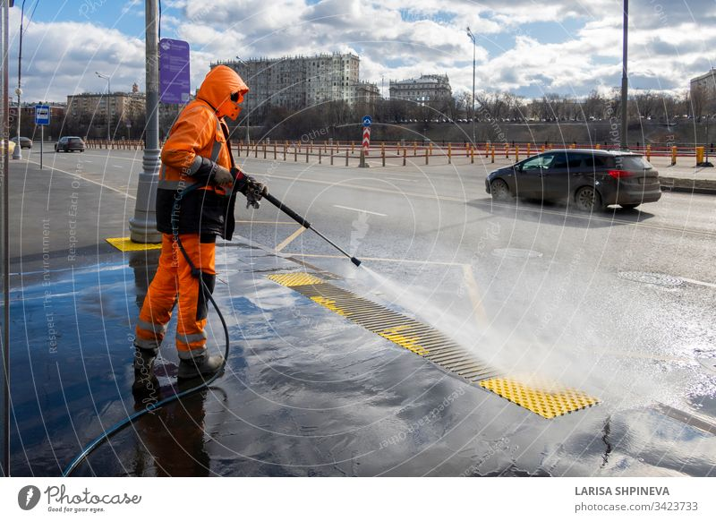 Road worker cleaning city street with high pressure power washer, cleaning dirty public transport stops, Moscow, Russia industrial water equipment man service