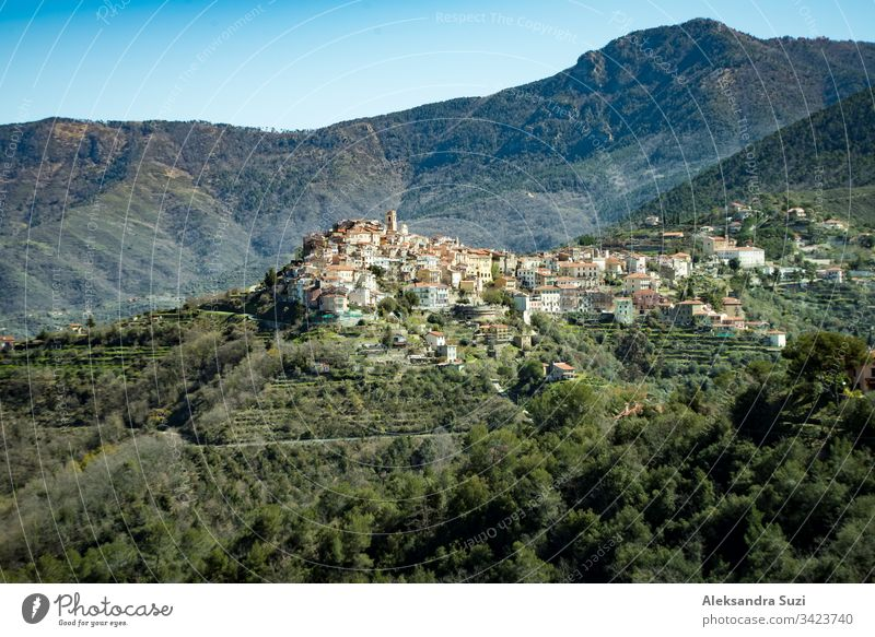 Panoramic top view of Alps mountains in fog and clouds, valley with clouds. Green slopes and fields. Almond trees in bloom. Medieval buildings of Perinaldo town, Liguria, Spring Italy