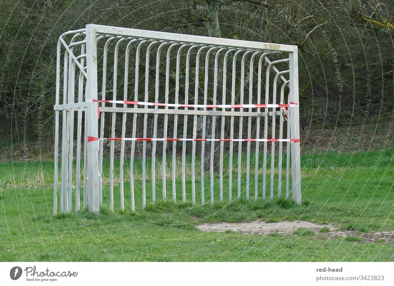 Metal soccer goal on the soccer field, which was closed with a flutter band because of Corona Soccer Goal Barred Green Playground Foot ball Outdoors forsake sb.