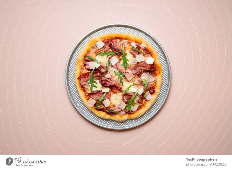 Pizza prosciutto on a baking tray. Whole ham pizza with arugula Italian above view carbs cheese and ham cuisine dinner european famous fast food finger food