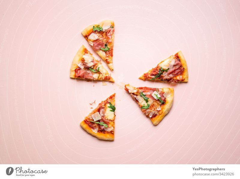 Pizza prosciutto slices on pink background. Italian  popular food arugula carbs cheese and ham cuisine dinner eating european famous fast food finger food