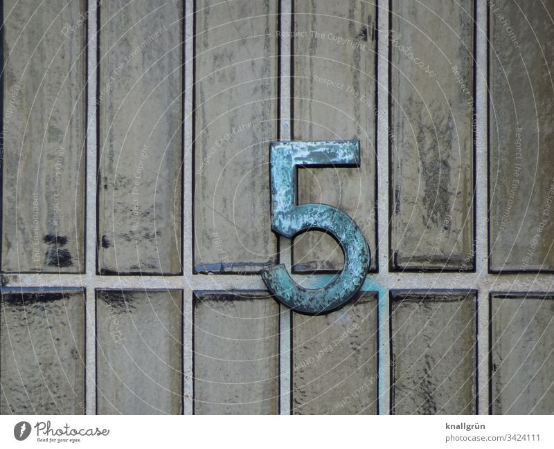 Wrought-iron house number 5 on grey-green glazed clinker brick slips House number Digits and numbers Detail Pattern Wall (building) Exterior shot Facade