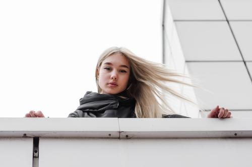 young girl with blond hair and black clothes against a gray building adult architecture autumn blonde city dreamy erase girl blonde hairstyle house lines look