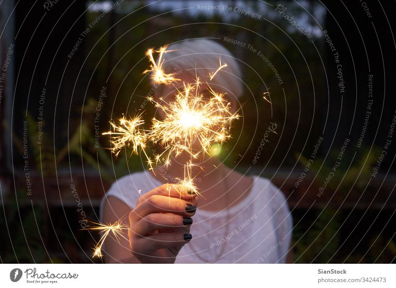 Blonde woman having fun with a sparkler. glowing person flame party forest winter woods lake year young holiday beautiful holding eve fire bengal hand xmas new