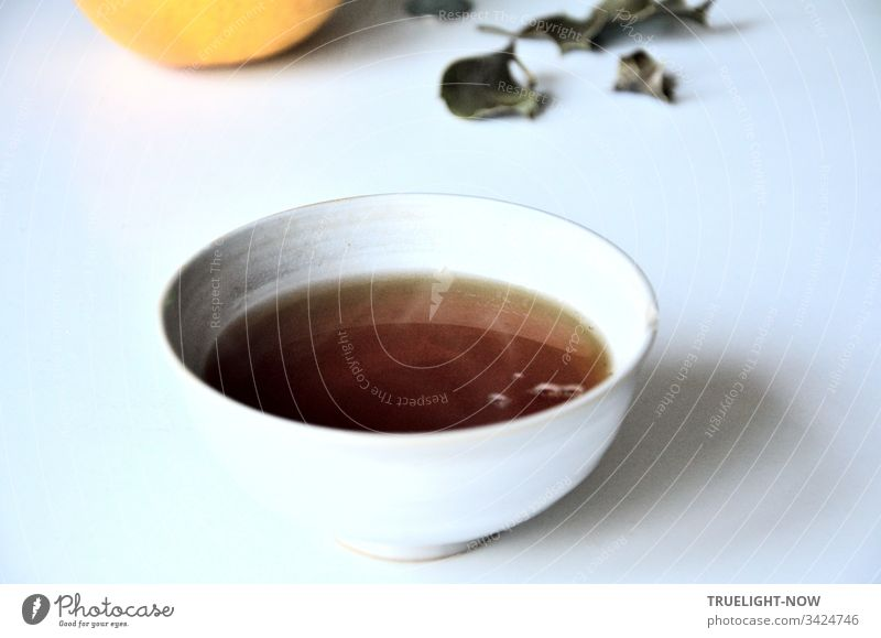 Freshly brewed Asssam tea in a light Chinese ceramic bowl on a white table with some fallen leaves and a grapefruit- Tea Black tea tea bowl Drinking White Brown