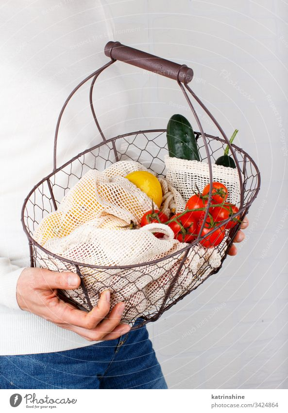 Woman keeps backet with vegetables and fuits in bags Zero waste jar glass jar basket concept body woman hands faceless textile farmers close up zero food
