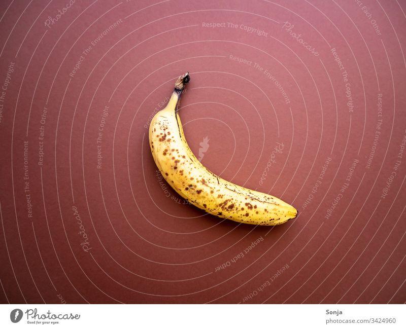 Überreife Banane mit Punkten auf einem braunen Hintergrund überreif punkte hintergrund draufsicht noch gut wegwerfen Lebensmittel Detail Food Organic produce