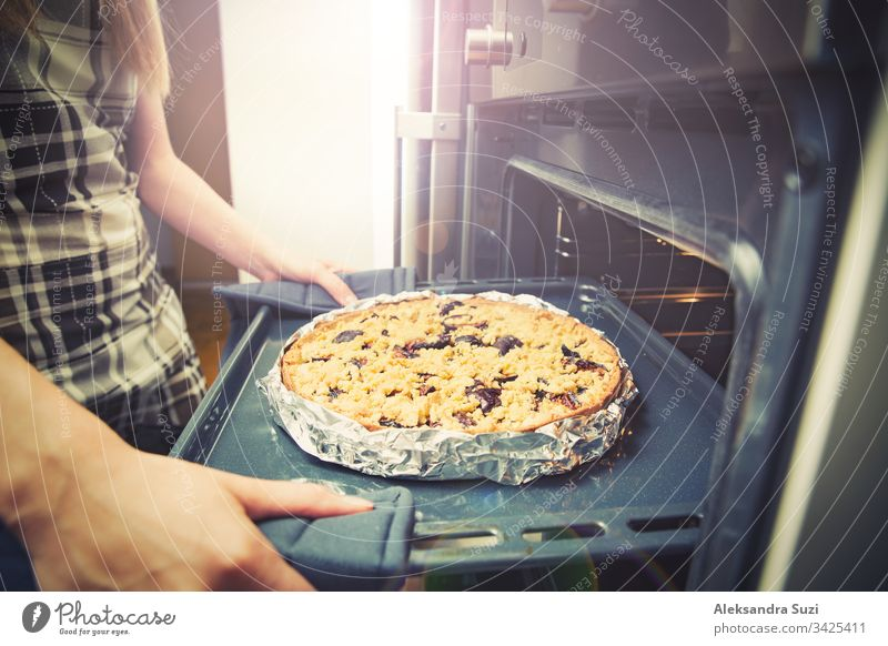Woman hands taking out tray with pastry from oven, closeup. Fresh homemade delicious plum pie. bake cake cook cooking cuisine dessert female food fresh fruit