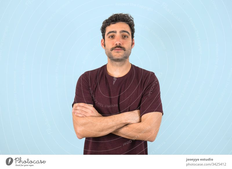 Portrait of brown, smiling, handsome man with mustache and purple t-shirt standing with crossed arms. Gray background. 30-40 years T-shirt adult attractive