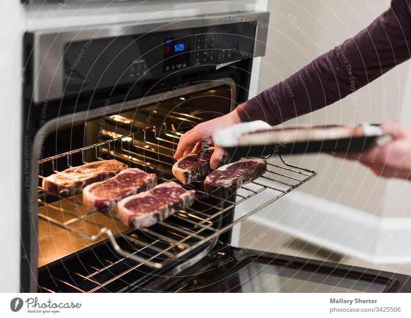 Man putting steaks into oven raw steak beef raw beef cooking cooking steak man man cooking cooking steaks in oven red meat cooking meat kitchen home