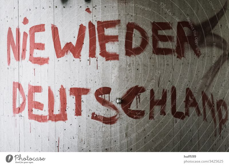 Slogan on the wall - Never again Germany Sign Way out Politics and state Criticism Red writing Strings Remark Characters Deserted Graffiti Society Exterior shot