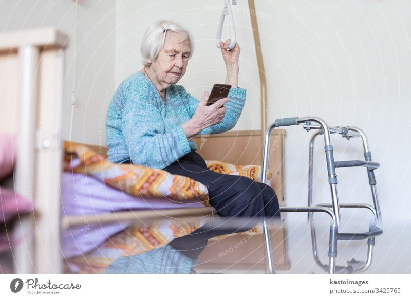 Elderly 96 years old woman reading phone message while sitting on medical bed supporting her by holder. senior home smart technology smartphone mobile