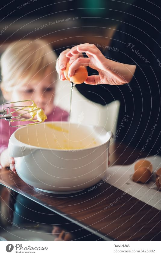 Baking a cake Child with mother Mother Cake eggs Parenting observantly watch Study Girl Toddler Infancy Deep depth of field Interior shot Human being Hand