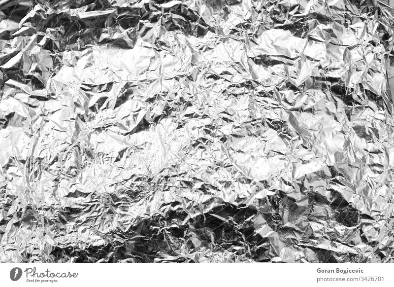 Close up of a wrinkled aluminum foil sheet silver gray shiny aluminium abstract paper texture background closeup alloy crumpled shine textured chrome backdrop