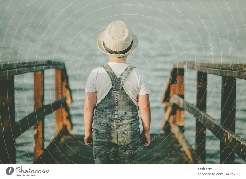 Back view of a Pensive child looking at the sea childhood nostalgic thoughtful Thought loneliness lonely expression freedom innocence portrait serious dream