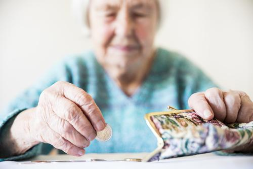 Concerned elderly woman sitting at the table counting money in her wallet. senior pensioner poverty retirement old empty coins background miserable broke lonely