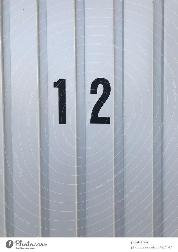 Black number twelve 12 on garage door Garage Goal Corrugated sheet iron Garage door Exterior shot Deserted Colour photo Monochrome Copy Space bottom Day