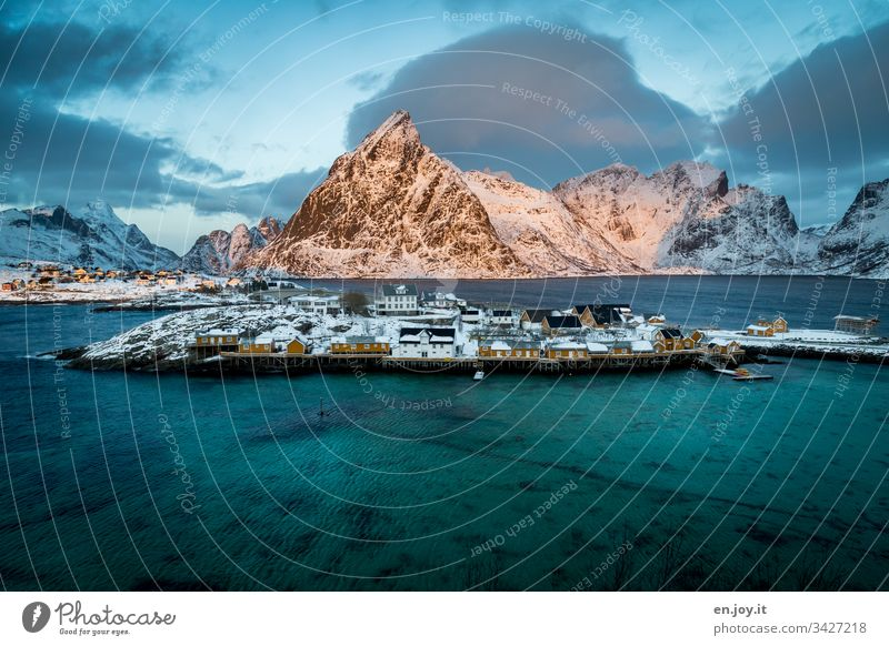 "Fishing village on the fjord in front of a snowy mountain sacrisoy Lofoten,"" Lofoten Islands Yellow Travel photography Idyll Vacation home Rorbuer Reinefjorden"