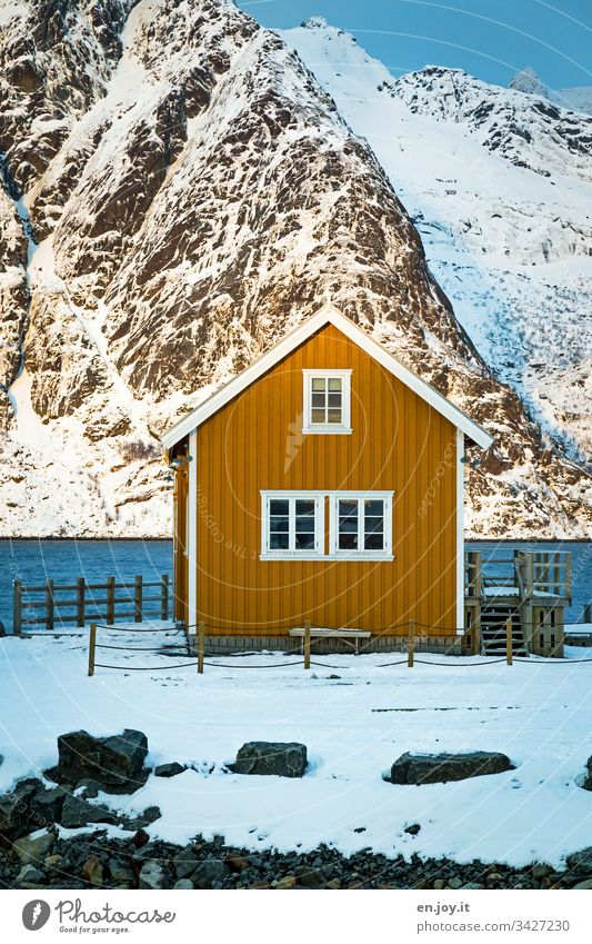 Small yellow house by the fjord in front of snow-covered mountains North Relaxation Winter vacation Ocean Snow Central perspective Environment Vacation & Travel