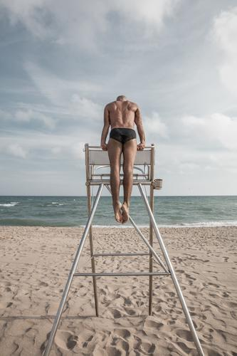 Gymnast at the stand from behind Man Beach Lifeguard Chrome Chair coached Strong exercise Waves Sand Horizon Clouds Swimming trunks muscle Acrobatics