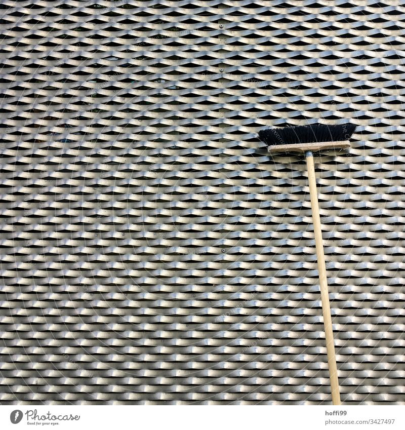 Broom in front of a metal facade Broomstick Broom closet Structures and shapes cladding of facades Facade Architecture structure Metal Honeycomb pattern Waves
