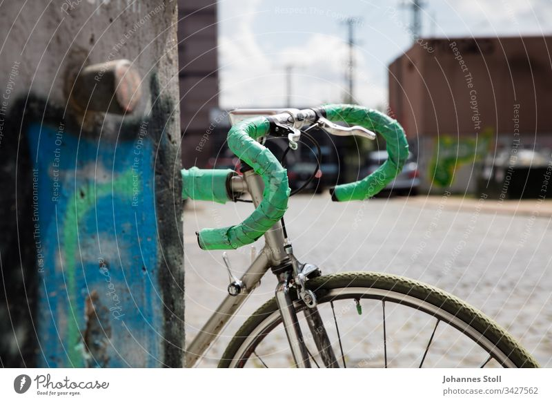 Vintage road bike with green handlebar tape leaning against graffiti wall Racing cycle Retro vintage Steel Aluminium Bicycle Hipster urban Town Transport