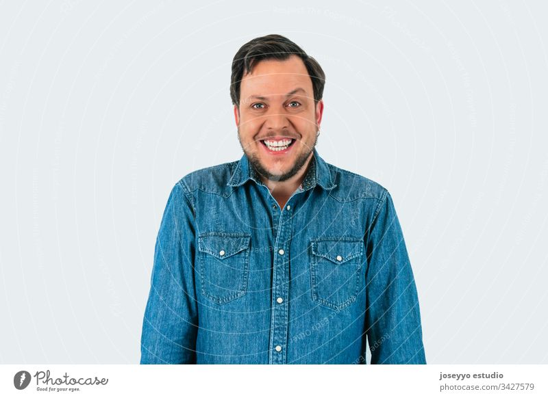 Portrait of young man smiling and looking at camera with one eyebrow raised. Denim shirt and isolated gray background. 30-40 years Raise the eyebrow absurd
