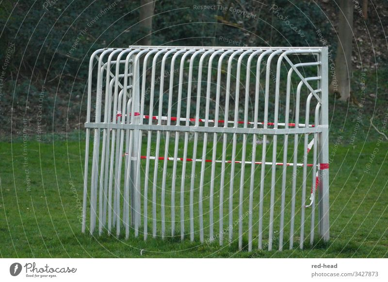 Metal football goal from behind on the football field, which was closed with a fluttering band because of corona Soccer Goal Barred Green Playground