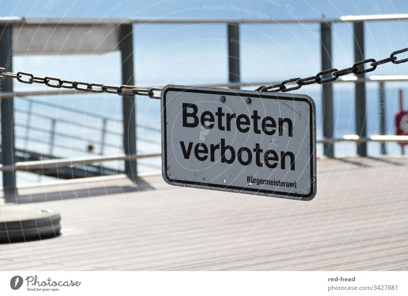 No trespassing - sign on a chain link in front of the landing stage, railing in the background, light blue sky and lake Lake Signs and labeling Handrail Text
