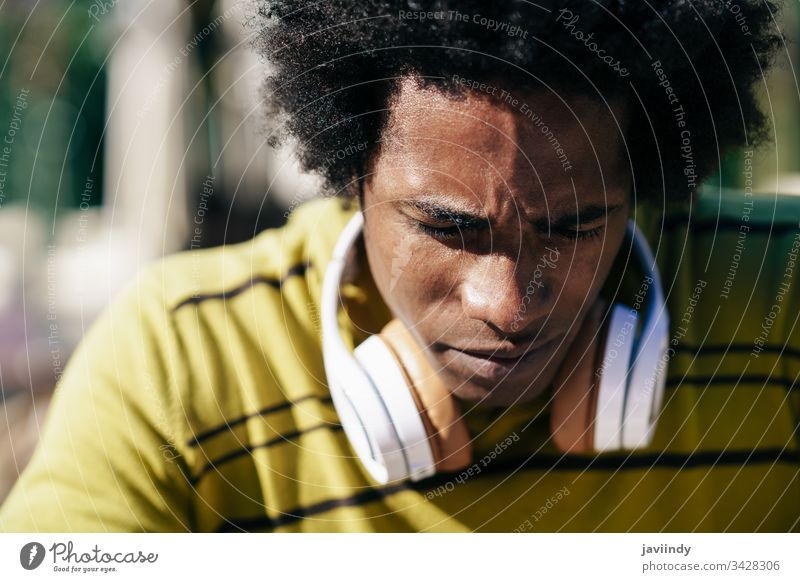 Close-up portrait of serious black man looking down. afro concerned thoughtful pensive hair african male face adult american person casual guy attractive