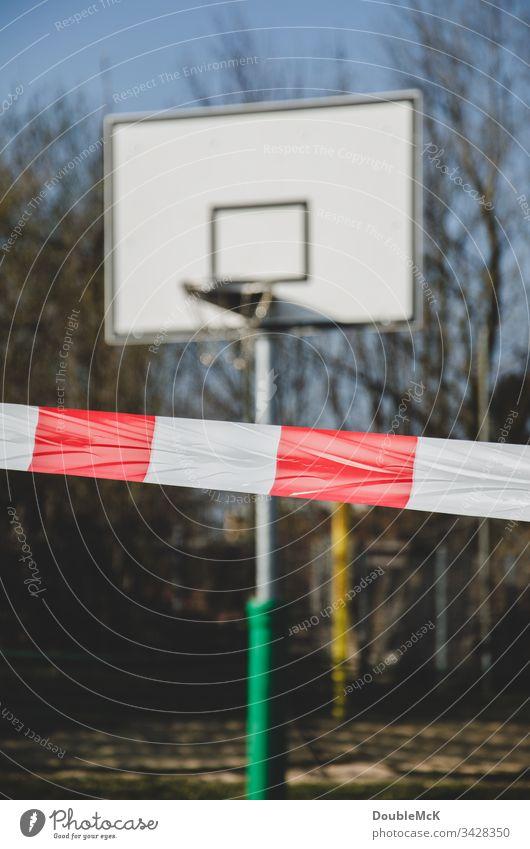 Playing prohibited - Basketball court closed due to coronavirus cordon barrier tape blocking Basketball arena Basketball basket Day Exterior shot Colour photo