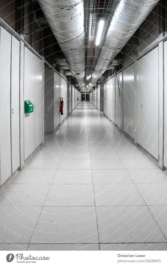 Interior shot of long empty corridor in industrial building with thick thermal pipes on running along the ceiling buildings property hallway long corridor